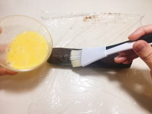 Brush the dough log with egg liquid lightly