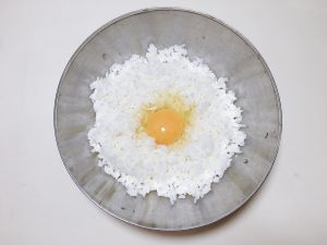 Add white rice and egg in a bowl