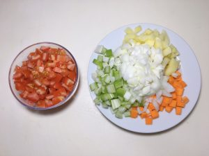 Dice the carrot, onion, tomatoes, potatoes, and celery